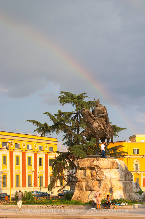 The statue of the 15th century warrior and national hero Skanderburg Skanderbeg on a huge stone base. A colourful rainbow in the sky and administrative buildings in the background. The Tirana Main Central Square, Skanderbeg Skanderburg Square. National Tourist Organisation in the background. Tirana capital. Albania, Balkan, Europe.