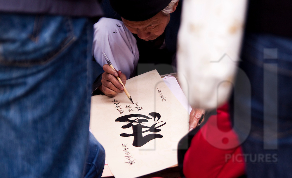 Close to the Temple of Literature, calligraphers show their skills. Those artists write chinese characters in a decorative hand, using large paintbrush and black ink.