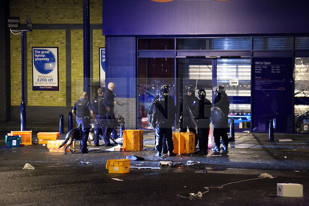 © Licensed to London News Pictures.  FILE PICTURE DATED 08/08/2011 LONDON, UK. Police dogs are seen at the front of the Brixton Branch of UK electrical chain Currys during a search for any looters left inside after a police cordon was established around the shop. The looting took place after a second night of violence hit several parts London. Photo credit: Matt Cetti-Roberts/LNP