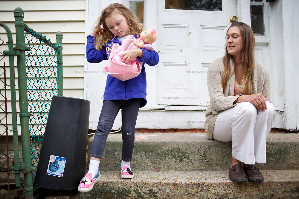Julia with her daughter Annabella, age 5, on the doorstep of their home. Julia's apartment was provided with the assistance of the Supportive Housing program in Connecticut. <br /> <br /> Julia, 33, was raised in an abusive household and she entered foster care at the age of 9. Julia's mother was mentally ill and her father was sent to prison. As a teenager, Julia began suffering from depression. Lonely and in search of company, Julia entered a six-year, often-abusive relationship when she was only 13 years old. By the time she was 15, Julia had moved in with her older sister who became her foster parent. Julia's depression got worse, she started self-medicating with cannabis and at age 17 dropped out of school. Two years later, her mother suddenly died and Julia found life increasingly unbearable. She contemplated suicide but didn't seek help for her depression. Then Julia met Richard with whom she has shared a relationship that continues 14 years later. <br /> <br /> During what Julia describes as a traumatic period three years ago, she and Richard were arrested in a domestic dispute. The couple, by this time parents to a two year old daughter called Annabella, lost their apartment and Julia once again moved in with her sister, taking Annabella with her. The Department of Children and Families (DCF) were alerted and encouraged Julia to seek the assistance of the Supportive Housing program. In November 2014, Julia was introduced to Rose who became her case manager at the program. By January 2015, Rose had helped Julia secure an apartment subsidised by Supportive Housing. Rose offered emotional and material support, using funds to help Julia furnish her new home that was close to amenities including a park and laundromat. <br /> <br /> Rose introduced Julia to United Community Family Services who provided bus passes, signed her up with social security, disability allowance, state cash-assistance, counselling and medication-management. Never having lived with the sup