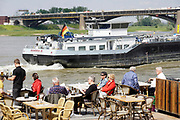 Nederland, Nijmegen, 29-5-2019Een binnenvaartschip vaart dicht langs de rand van de Waalkade waar mensen op een terrasje zitten .Foto: Flip Franssen
