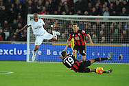 Andre Ayew of Swansea city (l) is sent flying after a tackle from Junior Stanislas of Bournemouth. Barclays Premier league match, Swansea city v AFC Bournemouth at the Liberty Stadium in Swansea, South Wales  on Saturday 21st  November 2015.<br /> pic by  Andrew Orchard, Andrew Orchard sports photography.