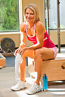 Portrait of a physically fit woman in a weightroom / healthclub setting.