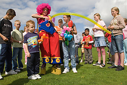 Clown at a Parklife summer activities event balloon modelling with a group of children,