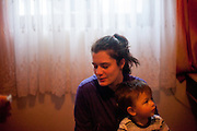 Irma - the wife of former refugee Elvis Causevic - holding their son Aldin (1 1/2) in the living room at the  families house in Hadžići. The family settled here after the war ended in Bosnia. Hadžići is a town and a municipality located about 20 km south west of Sarajevo city but within the Sarajevo Canton of Bosnia and Herzegovina. According to the census of 2013, Hadžići municipality has a population of 23,891 residents.