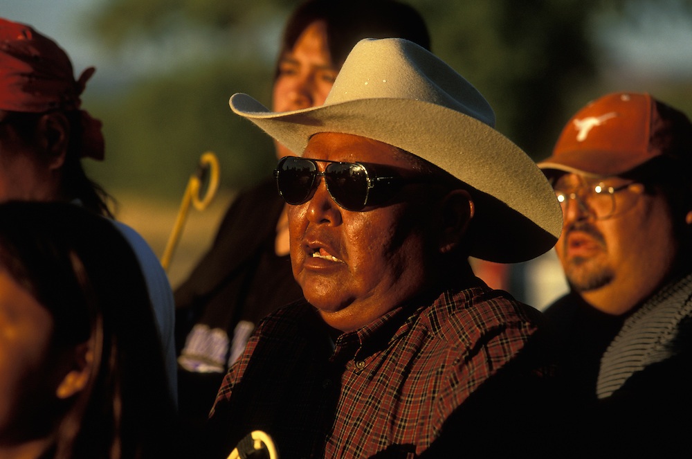 An Apache medicine man, surrounded by his assistans, sings and beats his drum at a Sunrise Dance, a first menstruation rite, on the San Carlos Apache Indian Reservation in Arizona, USA. The Sunrise Dance is held during the summer, within one year after the girl has had her first menstruation, and lasts for four days. The ceremony is an enactment of the Apache creation myth and during the rites the girl 'becomes' Changing Woman, a mythical female figure, and comes into possession of her healing powers. The rites are supposed to prepare the girl for adulthood and to give her a long and healthy life without material wants.