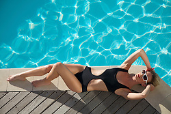 Elevated view of a woman sunbathing on the edge of a swimming pool