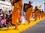 """02 JANUARY 2015 - KHLONG LUANG, PATHUM THANI, THAILAND: Monks walk through the crowd at Wat Phra Dhammakaya on the first day of the 4th annual Dhammachai Dhutanaga (a dhutanga is a """"wandering"""" and translated as pilgrimage). More than 1,100 monks are participating in a 450 kilometer (280 miles) long pilgrimage, which is going through six provinces in central Thailand. The purpose of the pilgrimage is to pay homage to the Buddha, preserve Buddhist culture, welcome the new year, and """"develop virtuous Buddhist youth leaders."""" Wat Phra Dhammakaya is the largest Buddhist temple in Thailand and the center of the Dhammakaya movement, a Buddhist sect founded in the 1970s.   PHOTO BY JACK KURTZ"""