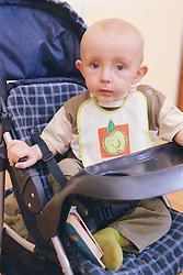 Close up portrait of baby boy sitting in pushchair,