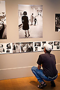 An intruiged exhibitgoer examines the pages of the 1966 Yearbook artwork in Faulconer Gallery during the 2012 Alumni Reunion.
