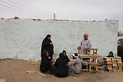 Locals talk in a quiet place at the weekly market at Qurna, a village on the West Bank of Luxor, Egypt. Holding seemingly serious talks about an important local matter or a business issue, the people sit on the dirt path alongside a rough wall. Amidst the bustle of this busy regular event, people from many miles around have come to trade and buy their provisions.