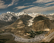 A full moon rises over the Passu village and its glacier, and the Karakoram Highway snakes its way through the landscape.