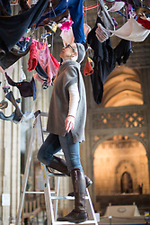 "@Licensed to London News Pictures 22/02/2018. Canterbury, UK. Artist Arabella Dorman makes the final adjustments to her installation ""Suspended"" in the nave of Canterbury Cathedral in Kent today. This evocative artwork highlights the plight of refugees around the world and is made up of hundreds of items of refugee clothing found mainly on the beaches of the Greek Island of Lesbos. Photo credit: Manu Palomeque/LNP"