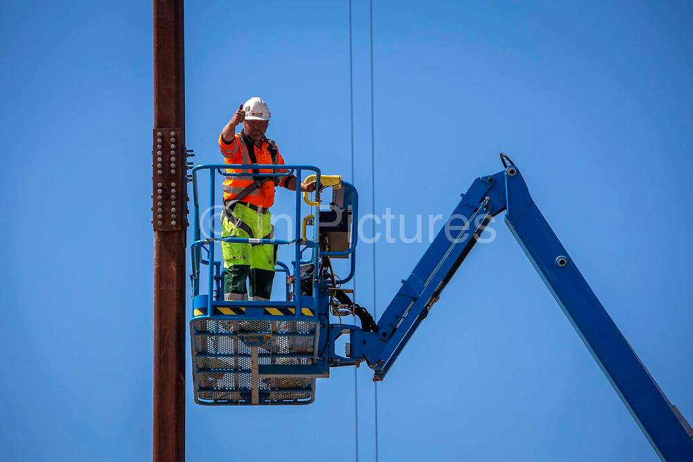 Workmen carry out the reinstallation of 'Out of Tune' by AK Dolven with a cherry picker and a crane on the 21st of May 2020 on the seafront in Folkestone, United Kingdom. This sound installation was originally part of the Folkestone Triennial Art festival of 2011.  A K Dolven's installation 'Out of Tune' features a sixteenth century tenor bell from Scraptoft Church in Leicestershire, which had been removed for not being in tune with the others. Itis suspended from a steel cable strung between two 20m high steel beams, placed 30m apart. The bell was cast by Hugh Watts in the seventeenth century in Leicester. The Watts family were the leading bell founders in that city in the early 17th century. In all, they were responsible for almost two hundred castings for churches in the county. Hugh Watts prospered and was the Mayor of Leicester when King Charles 1st visited the city in 1634.