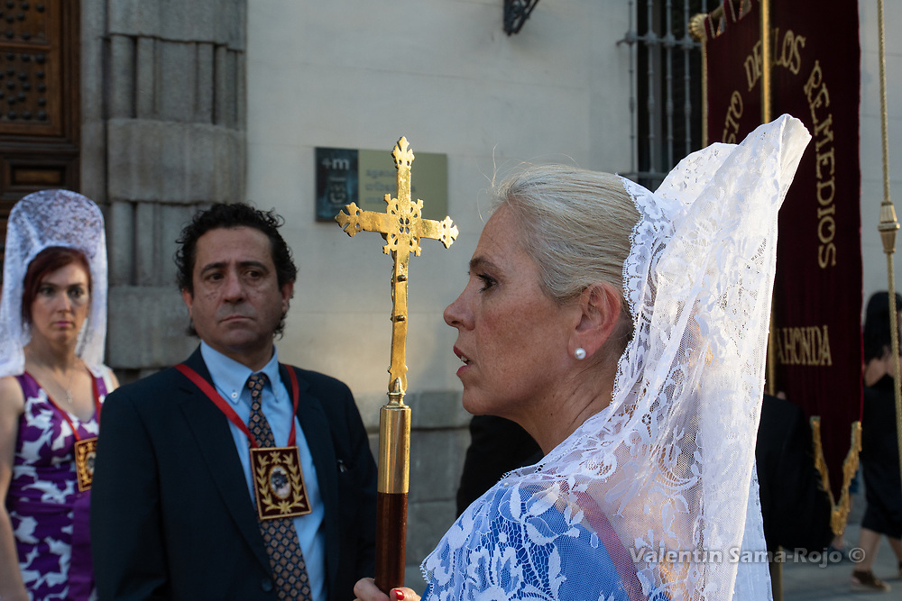 Madrid, Spain. 23rd June, 2018. Woman wearing a white shawl and a comb and carrying a stick with a cross, looking to the procession. © Valentin Sama-Rojo