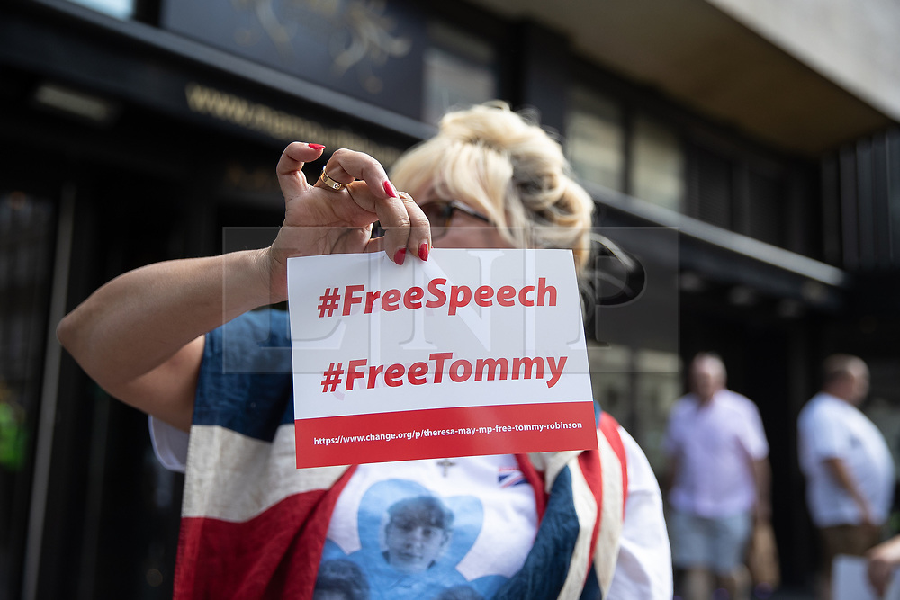 """© Licensed to London News Pictures. 10/06/2018. London, UK. A woman holds up a """" FreeTommy """" flyer in support of jailed former EDL leader Tommy Robinson , as part of a counter demonstration to the annual Al Quds day march in support of the Palestinian cause, in central London. Photo credit: Joel Goodman/LNP"""