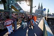 In Keulen passeert een bezorger van Lieferando.de, de Duitse versie van Thuisbezorgd.nl, voetgangers over de brug met de liefdessloten. Koppels hangen sloten aan de brug om te laten weten dat ze van elkaar houden. Op de achtergrond de Dom van Keulen.<br /> <br /> In Cologne a cycling food delivery guy passes tourists near the locks of love hanging on the bridge.
