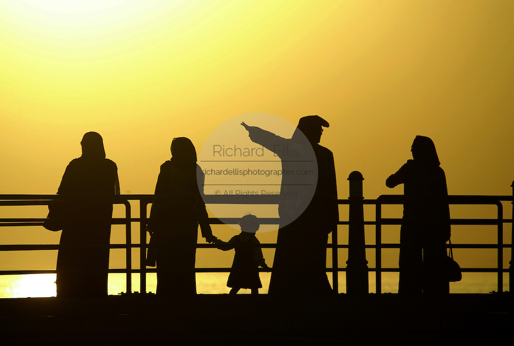 Kuwaities in traditional attire walk along the dock on the waterfront as the sun sets over the Persian Gulf.