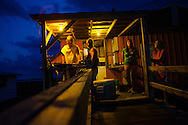 People at a fishing camp preparing dinner with thier catch from the day on Isle de Jean Charles. 3