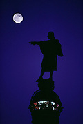 Silhouette of Columbus Monument with full moon, Barcelona, Spain.