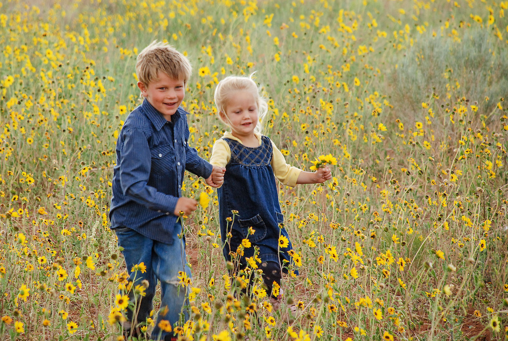 Boy and girl running, holding on to hands in a field of sunflowers.