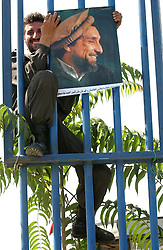 KABUL,AFGHANISTAN - SEPT. 8: An Afghan policeman hangs up a poster of Ahmad Shah Massoud September 8, 2002 in preparation for the events tied to tomorrow's  anniversary of his death in Kabul, Afghanistan. (Photo by Ami Vitale/Getty Images)