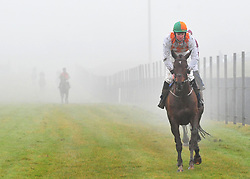 Runners emerge from the fog after pulling up in the Fred Kenny Handicap Steeplechase, during BoyleSports Irish Grand National Day of the 2018 Easter Festival at Fairyhouse Racecourse, Ratoath, Co. Meath