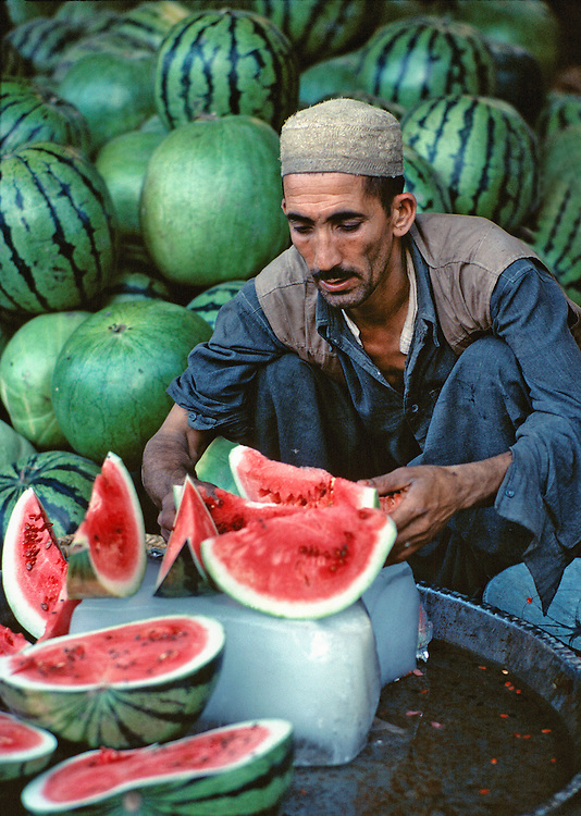 A melon vendor sells slices of watermelon in the bazaar in Peshawar, Khyber Pakhtunkhwa, Pakistan.