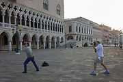 Photographers bend their knees  outside the Doge's Palace in Piazza San Marco, Venice, Italy. It is dawn in the Italian city on the sea and the wide expanse of Piazza Marco with the Doge's Palace on the left, two men stand with legs apart to take their pictures of an empty square in the heart of Venice and where, in a few hours, the pavement will be crowded with humanity as the influx of tourists who, in their own way, flood the narrow streets and smaller canals with gondolas. The light is soft and the air cool on this midsummer morning during a heatwave - the best time to be here.