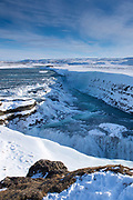 Gushing, flowing glacial river water at falls of Gullfoss Waterfall and snow-covered mountains in glacial landscape of South Iceland