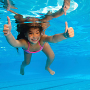 Young girl of 7 swimming underwater gives the Thumbs up sign