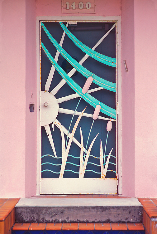 A Tropical Deco screen door on a single family home in the Flamingo Park area of Miami Beach, Florida. The pressed metal design -- featuring sunbeams,  tropical vegetarion and ocean waves -- probably dates back to the late-1930s or early 1940s. Screen doors like this were typical in South Florida before airconditioning became commonplace. This photograph was made in 1993, but as of 2018, this remarkable vintage door still survives there.