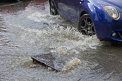 © Licensed to London News Pictures 20/07/2021. Orpington, UK. An overflowing drain in the road in Orpington. Heatwave thunderstorms hit Orpington in South East London causing roads to flood and drains to overflow. Photo credit:LNP