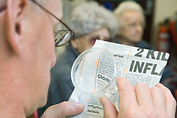 A Man reading a newspaper with a magnifying glass at the Nottingham Royal Society for the Blind (NRSB),