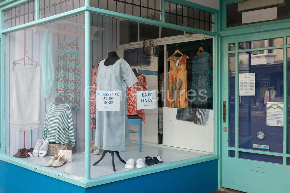 A high street charity shop selling ladies fashion styles in the window, shows customers the one-way system owners have introduced as shops are re-opening after months of Coronavirus pandemic lockdown, on 19th July 2020, in Whitstable, Kent, England.