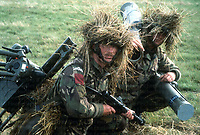 Soldiers of the 1st Battalion Parachute Regiment on a NATO exercise in Europe. Both soldiers are carrying parts of a MILAN anti-tank weapon which weighed 7kg per missile and 24kg for the weapon system. The soldier on the left is also equipped with a STEN submachine gun. Photograph by Terry Fincher