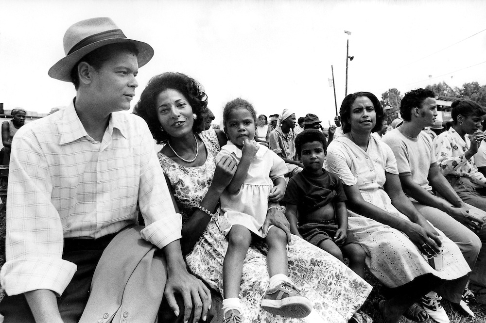 """Civil rights leader, politician, actor and former Chairman of the NAACP, Julian Bond, has died at age 75. Bond - left - sits with actress Pam Grier and extras during the filming of the 1977 feature film, """"Greased Lightning"""". The film starred Grier, Richard Pryor and Beau Bridges and chronicled the life of the first African American NASCAR driver - Wendell Scott."""