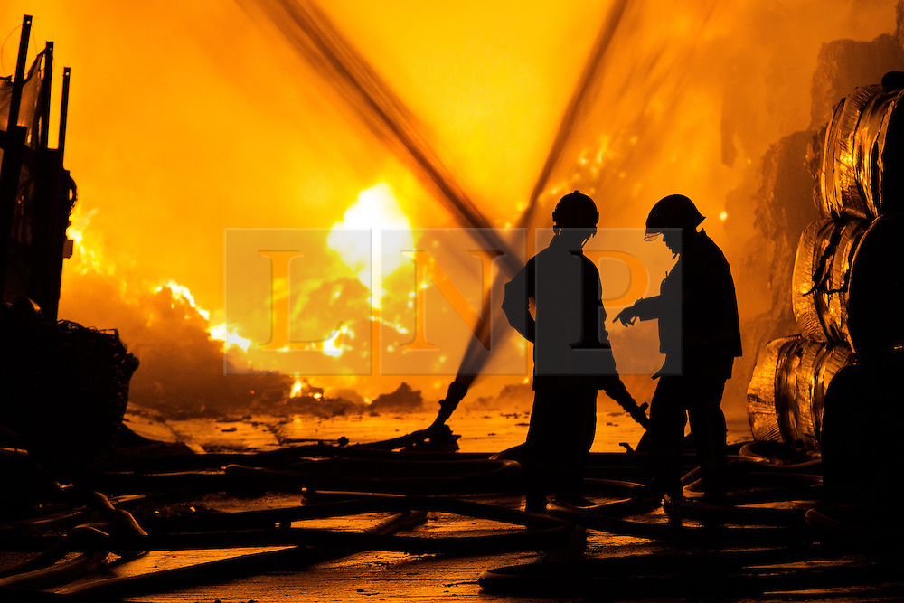 © Licensed to London News Pictures . 21/08/2013 . Stockport , UK . Firefighters silhouetted against the intense blaze at the J25 Recycling Centre in Bredbury , Stockport this morning (Wednesday 21st August 2013) where a building and bales of recyclable material are alight . The fire , which started late last night (20th August) is being tackled by more than 50 fire crew . The site , which is adjacent to a branch of Morrisons Supermarket and McDonalds , is off Junction 25 of the M60 motorway , exits for which are closed in both directions . Photo credit : Joel Goodman/LNP