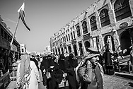 Arab men and women walking through the popular pedestrian area of Souk Waqif in Doha, Qatar.