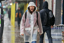 © Licensed to London News Pictures. 14/09/2021. London, UK. A woman wearing a raincoat yawns during rainfall in north London. A yellow weather warning for heavy rain is in place in London and parts of South East England. Photo credit: Dinendra Haria/LNP