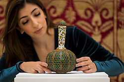 "© Licensed to London News Pictures. 23/10/2020. LONDON, UK. A staff member presents ""A Mughal gem-set and enamelled gold flask (Surahi)"", North India, Late 17thC/Early 18thC, set with over six-hundred emeralds, (Estimate GBP500,000-800,000), at Sotheby's, New Bond Street during the preview of their auction of Treasures from the Islamic World on October 27.  Photo credit: Stephen Chung/LNP"