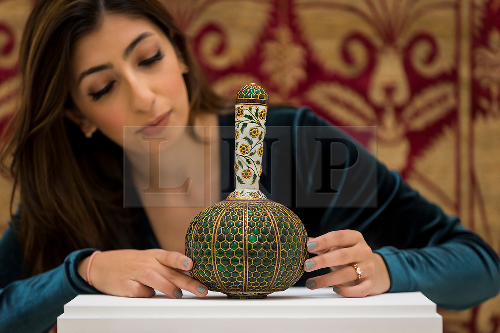 """© Licensed to London News Pictures. 23/10/2020. LONDON, UK. A staff member presents """"A Mughal gem-set and enamelled gold flask (Surahi)"""", North India, Late 17thC/Early 18thC, set with over six-hundred emeralds, (Estimate GBP500,000-800,000), at Sotheby's, New Bond Street during the preview of their auction of Treasures from the Islamic World on October 27.  Photo credit: Stephen Chung/LNP"""