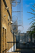 Security measures around the outside of one of the wings at HMP Wandsworth, including barbed wire and fencing. London, United Kingdom.