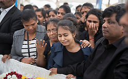 © Licensed to London News Pictures. 04/09/2016. London, UK. Relatives and friends mourn next to coffins of brothers Kenigan and Kobi Nathan at a joint funeral held at Winn's Common Park for five men who drowned at Camber Sands last month.  The five men: Kurushanth Srithavarajah, brothers  Kenigan and Kobi Nathan, Inthushan Sri and Nitharsan Ravi were all friends from London.  They got into difficulty in the sea of Camber Sands on August 24. Photo credit: Peter Macdiarmid/LNP