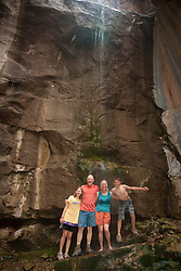 North America, United States, Colorado, Dinosaur National Monument, Green River (Gates of Lodore section), family under waterfall.  MR