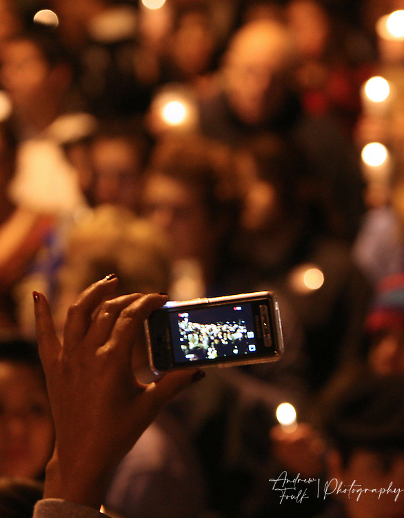 /Andrew Foulk/ For the North County Times/  .A mourner takes a photo of the crowd of the near one thousand people who came to Escondido High School Monday night   to remember Amber Dubois.