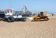 Caterpillar bulldozer machine and fishing boats on shingle beach, Aldeburgh, Suffolk, England, UK