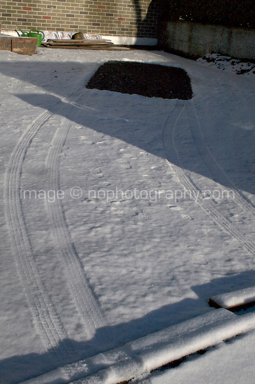 Snow covered driveway in Dublin Ireland with tyre tracks and gap in the snow where car was parked