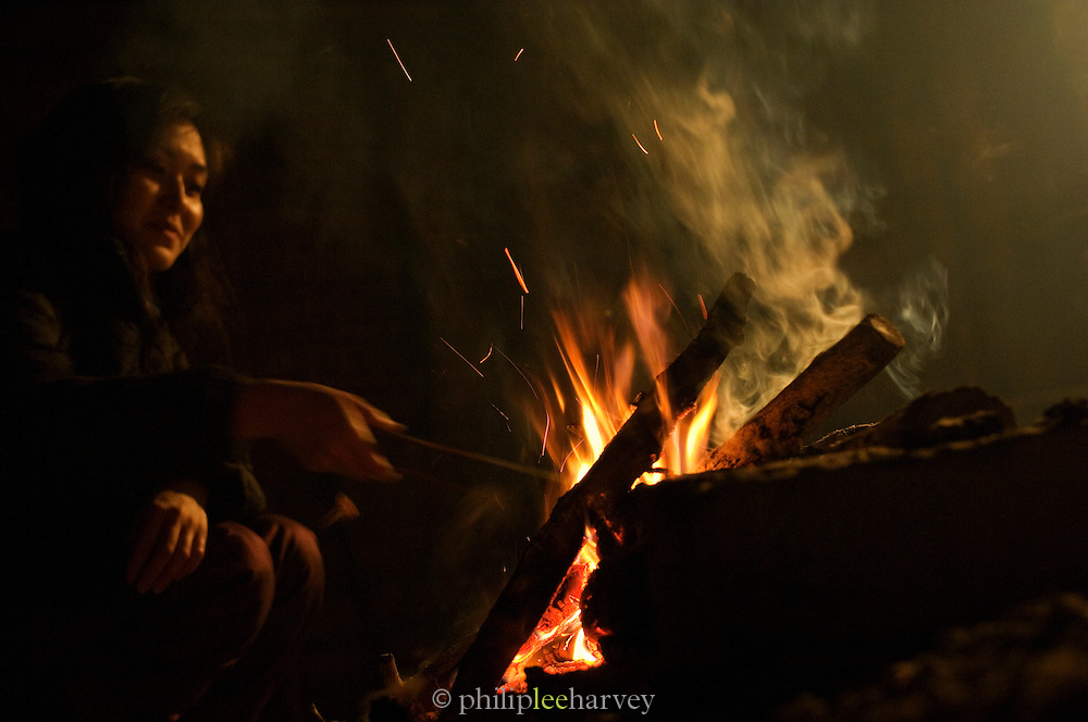 Ainu woman preparing food over a wood fire. The Ainu people are indigenous to Japan and Russia. Hokkaid?, Japan