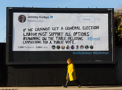 """© Licensed to London News Pictures. 14/02/2019. London, UK.  A woman walks past a new Jeremy Corbyn billboard from """"Led By Donkeys"""" that has been put up in Mr Corbyn's Islington constituency with a message asking for Labour party support on a pubic vote on Brexit. A previous billboard, errected in the same place on Monday was reportedly removed by Islington Council, who later replaced the blank board when challenged. Photo credit: Vickie Flores/LNP"""
